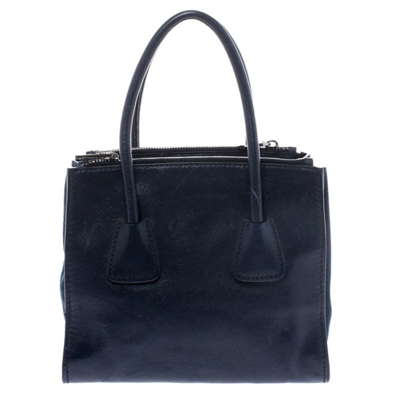 Add some effortless style and luxury to your everyday looks with this stunning Prada tote. Crafted in navy blue leather and suede, this bag can store all that you need in its large interior. The bag is equipped with the brand logo on the front, dual