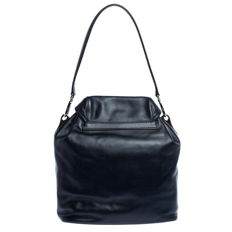 This lovely shoulder bag by Prada is stylish and functional. It has a leather exterior and carries a classic shade of navy blue. It is styled with a single handle, double pockets on the front, a spacious nylon-lined interior and silver-tone hardware