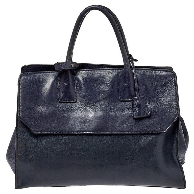 Feminine in shape and grand in design, this Sound Flap bag by Prada will be a loved addition to your closet. It has been crafted using leather and styled minimally with gunmetal-tone hardware. It comes with two top handles, well-lined compartments,