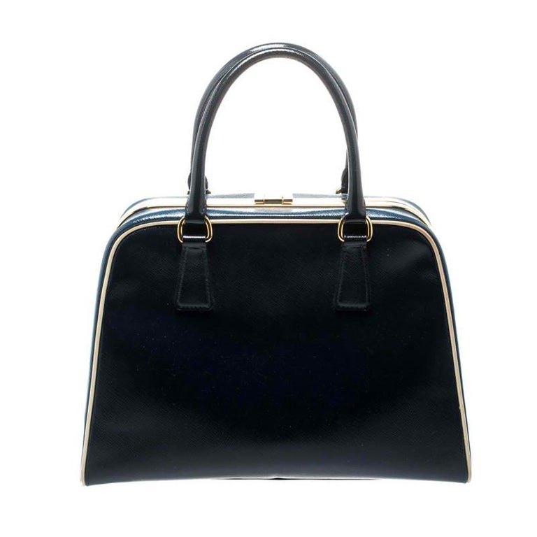 Stunning in appeal and high on style, this top handle bag by Prada will be a valuable addition to your closet. It has been crafted from patent leather and styled minimally with gold-tone hardware. It comes with dual top handles, protective metal