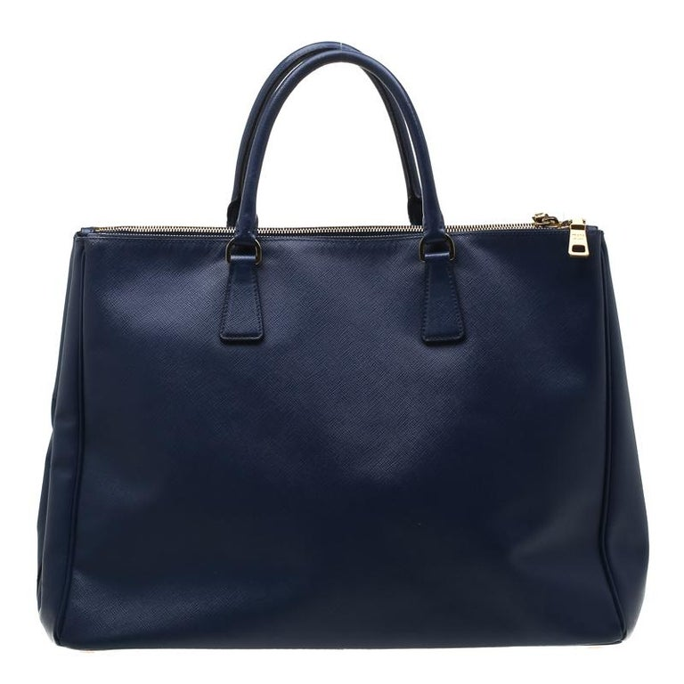 h Feminine in shape and grand on design, this Double Zip tote by Prada will be a loved addition to your closet. It has been crafted from leather and styled minimally with gold-tone hardware. It comes with two top handles, two zip compartments and a