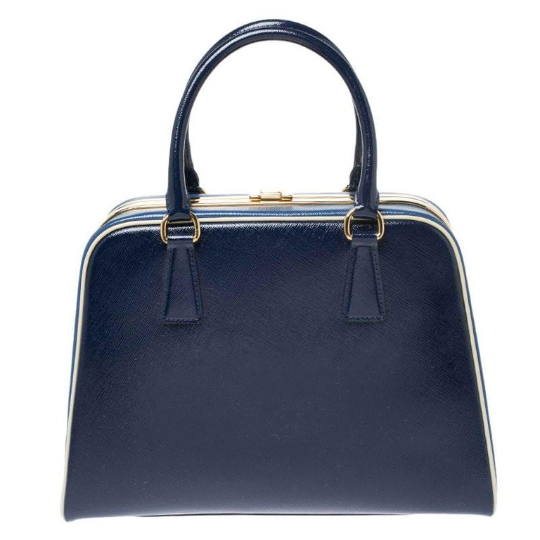 This stunning bag from Prada is crafted from leather and styled with gold-tone hardware. It features dual top handles and a metal lock which opens up to a perfectly sized leather interior ready to hold all your essentials. The accessory is complete