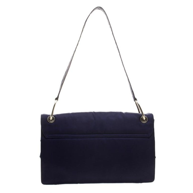 Prada brings us this lovely shoulder bag that has been crafted from nylon and designed with a flap that opens up to an interior capable of carrying all your important essentials. The piece is complete with a shoulder strap and the logo on the