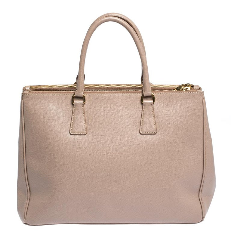 Feminine in shape and grand on design, this beige Double Zip tote by Prada will be a loved addition to your closet. It has been crafted from Saffiano Lux leather and styled minimally with gold-tone hardware. It comes with two top handles, two zip