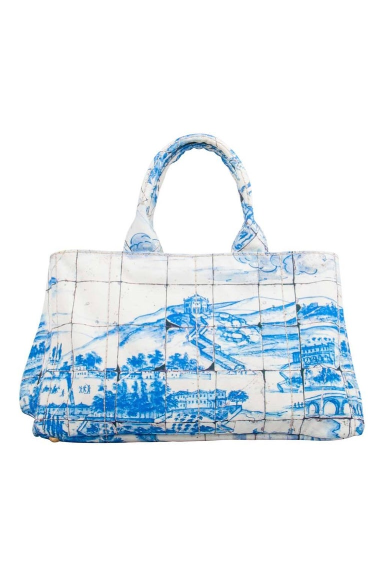 One of the most iconic designs from the house of Prada, this canvas Canapa tote bag is great to wear through the day or at your vacations whilst never compromising on style. Covered in prints of blue, this off-white bag features two handles, a