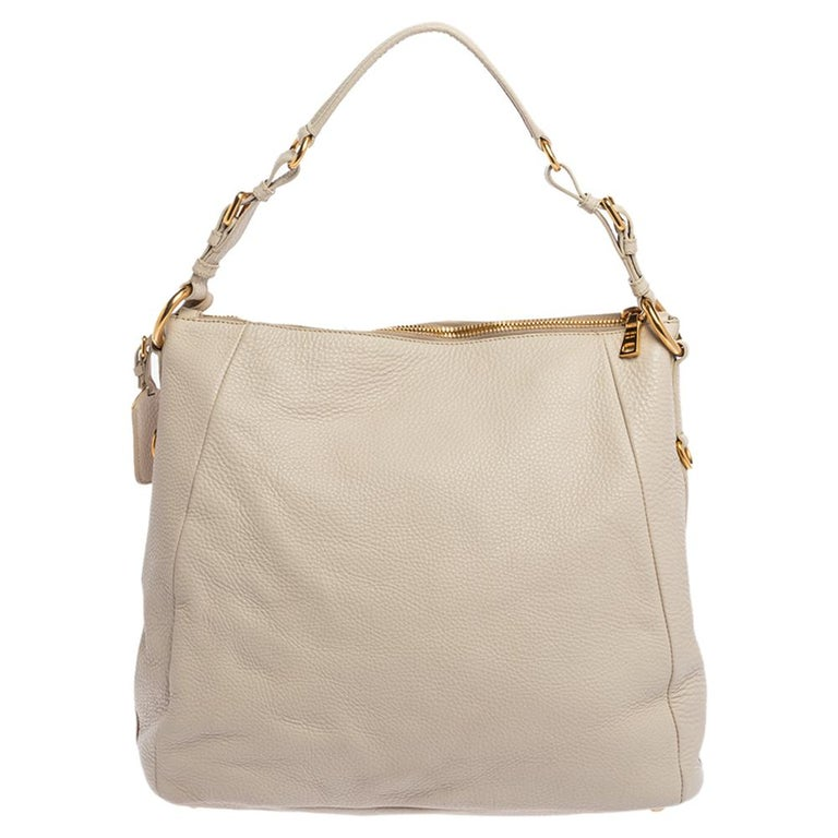 Flaunt this fantastic-looking hobo from Prada and give yourself a sophisticated look. The bag is held by a single handle and crafted from off-white hued leather. It comes with a nylon-lined interior that is secured by a zip. The hobo also features a