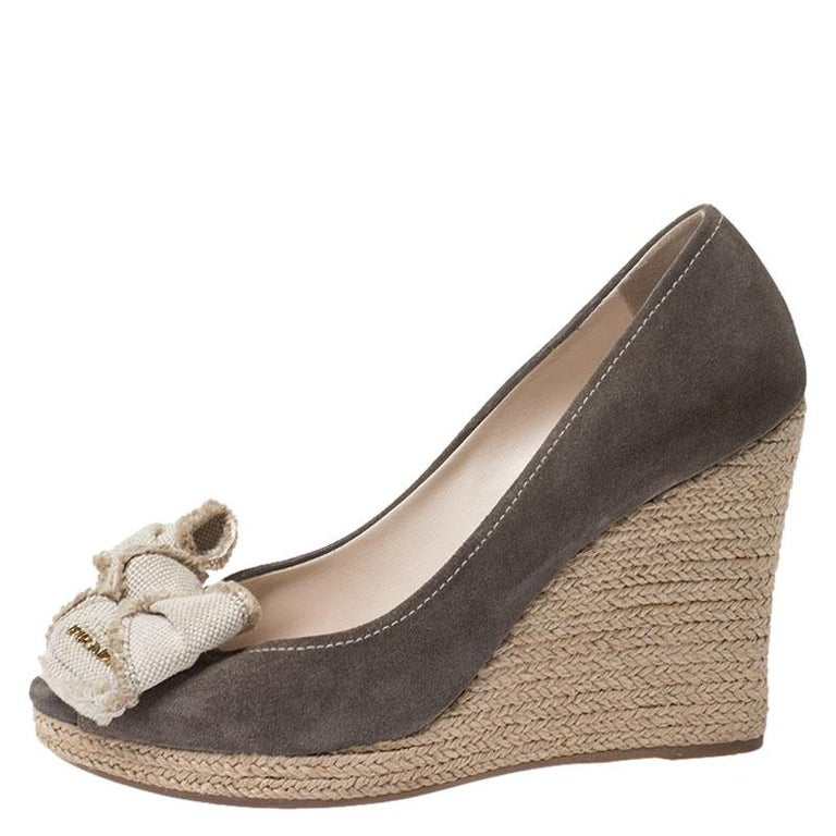 Complete your outfit with these Prada wedge pumps. They are made from olive green suede and feature peep toes, canvas bow details, espadrille wedge heels and leather-lined insoles. You are sure to enjoy both comfort and style with this pair.