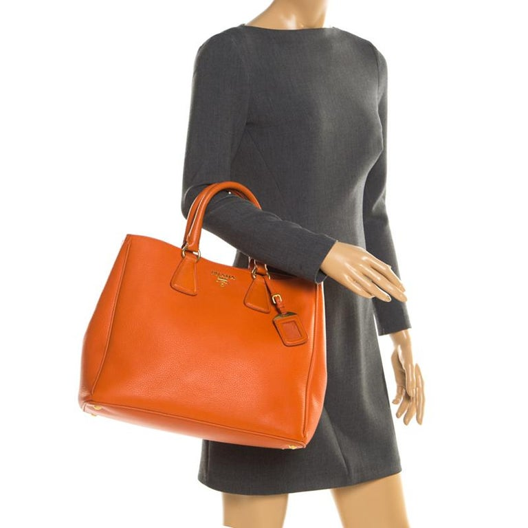 Masterfully crafted with orange leather, this bag will make a memorable addition. Finely lined with fabric, this is a one-stop fashion adornment for all your needs! This Prada bag is splendid for everyday use, and for special events. It is held by