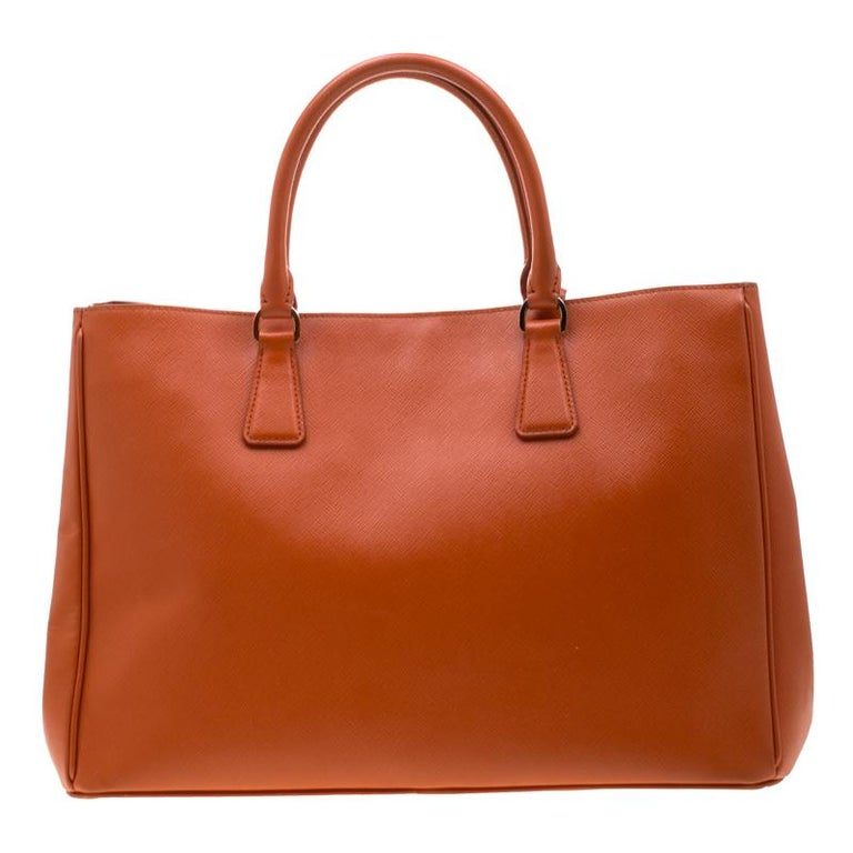 High on style, this Lux tote is an illustration of Prada's impeccable craftsmanship. Made from Saffiano leather, this orange tote features dual handles, a leather cover gold-tone key ring and protective metal feet. The nylon lined interior has ample