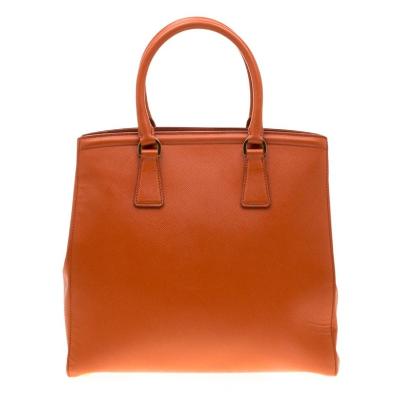 This sophisticated Parabole tote from Prada is crafted from Saffiano leather. The tote has an orange exterior featuring dual handles, a detachable shoulder strap and protective metal feet at the bottom. The fabric-lined interior houses an open