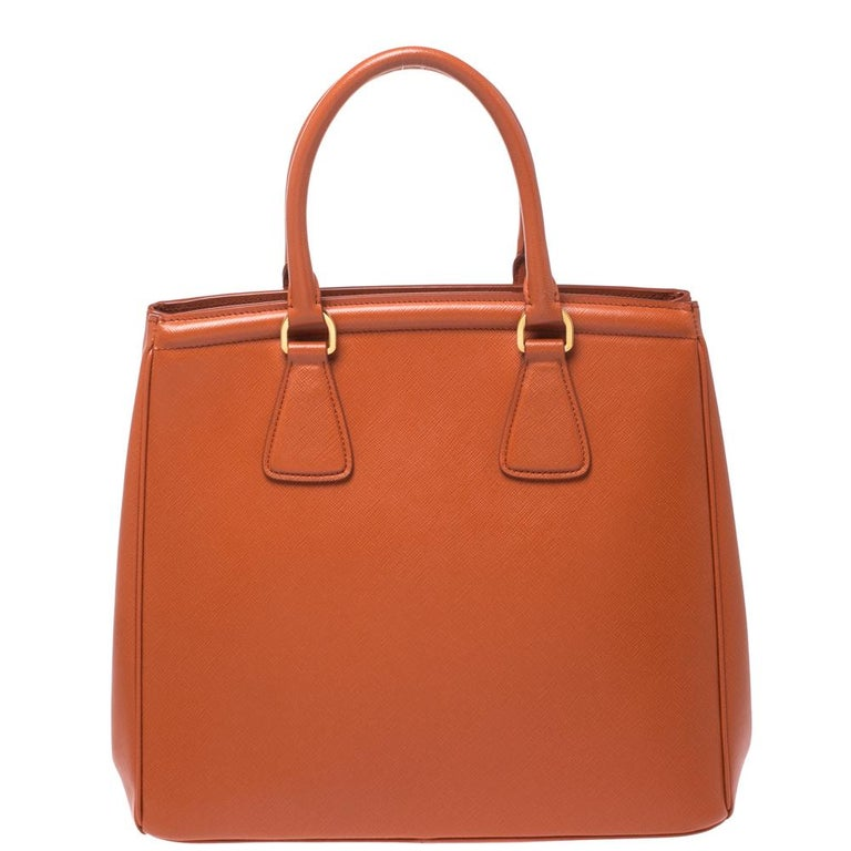 Masterfully created, this Prada tote bag is a style icon. Designed in a Saffiano Lux leather body in Italy, it exudes style and class in equal measures. This delightful orange piece is held by two top handles, is equipped with a brand logo,