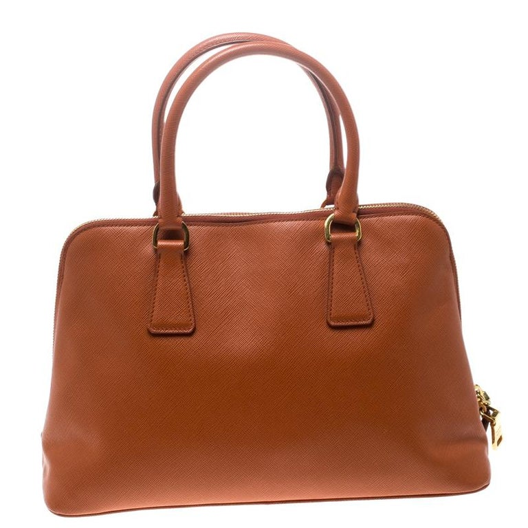 This stunning Promenade tote is high on appeal and style. Dazzling in a classy orange shade, it is crafted from Saffiano Lux leather and features two rolled handles and a name tag. The top zipper leads way to a nylon-lined interior with enough space