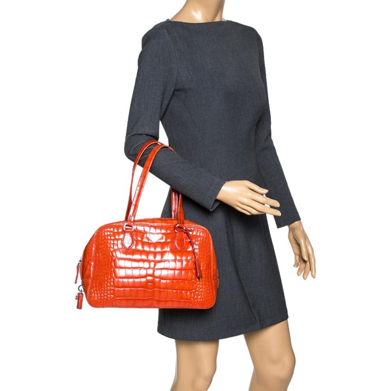 This elegant Bauletto bag from Prada is crafted from shiny croc-embossed leather and is perfect for your fashionable outings. The beautiful orange color is ravishing. The bag features splendid details in the form of dual top handles, a detachable