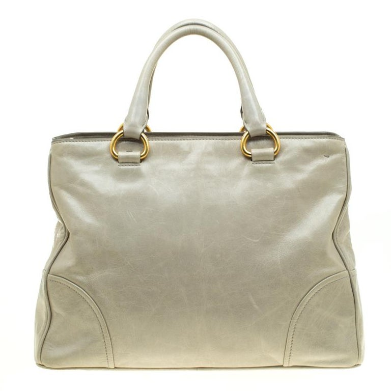 This pale green bag from Prada is very chic and stylish. It is crafted from glazed leather and radiates a shine making it look amazing. It features dual top handles with an attached tag accent, gold-tone brand logo at the front and protective metal