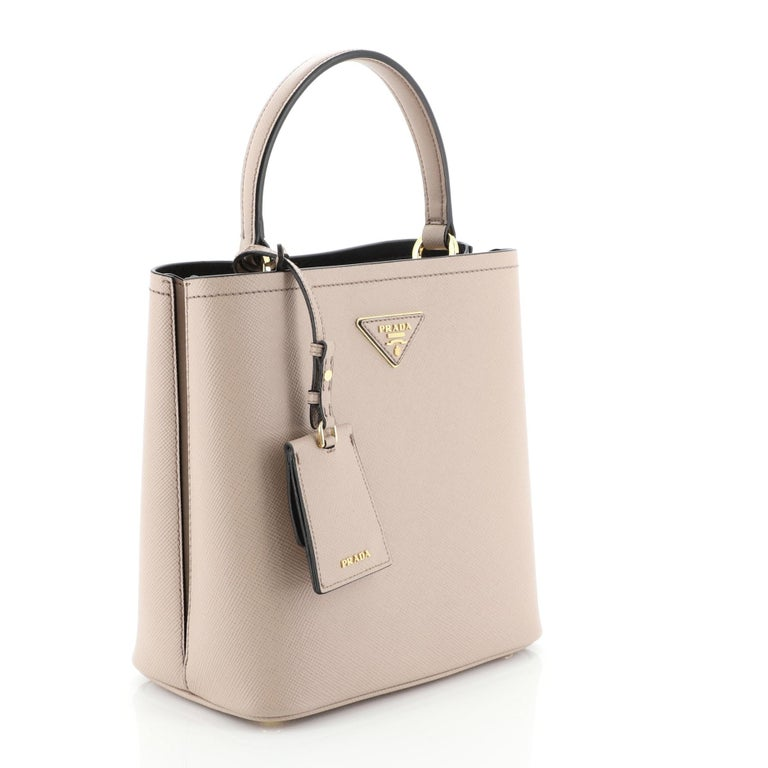 This Prada Panier Bucket Bag Saffiano Leather Medium, crafted in pink saffiano leather, features a leather top handle and gold- tone hardware. Its wide open top showcases a black leather interior divided into two compartments.   Condition: