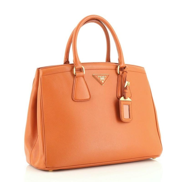 This Prada Parabole Handbag Saffiano Leather Medium, crafted in orange leather, features in dual rolled leather handles, protective base studs and gold-tone hardware. It opens to an orange fabric interior with middle zip compartment including a side