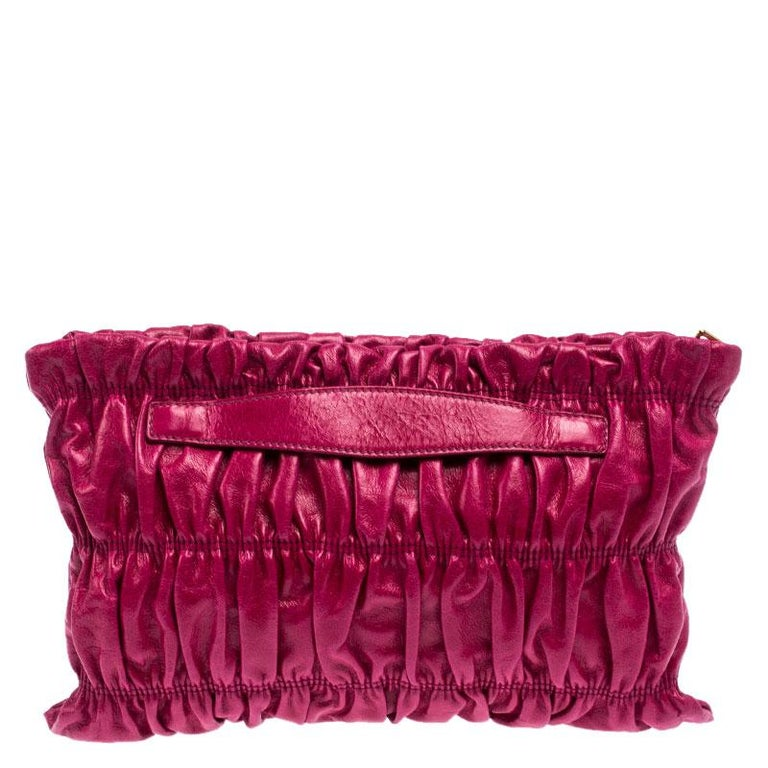 Have all eyes on you when you flaunt this stylish clutch by Prada. Crafted from pink-colored leather, it carries a gathered design all over the front. The Italian made beauty has a top-zip closure that opens to a nylon-lined interior to hold your