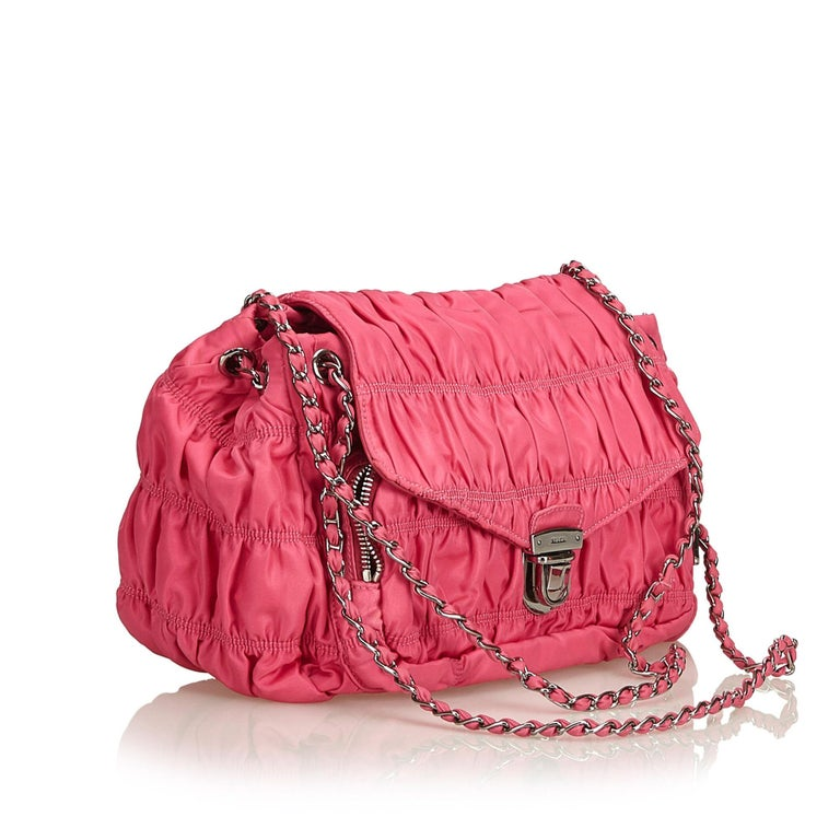 This shoulder bag features a gathered nylon body, chain-link straps, front flap with push lock closure, exterior zip pocket, interior zip and slip pockets. It carries as A condition rating.  Inclusions:  Dust Bag  Dimensions: Length: 17.00 cm Width: