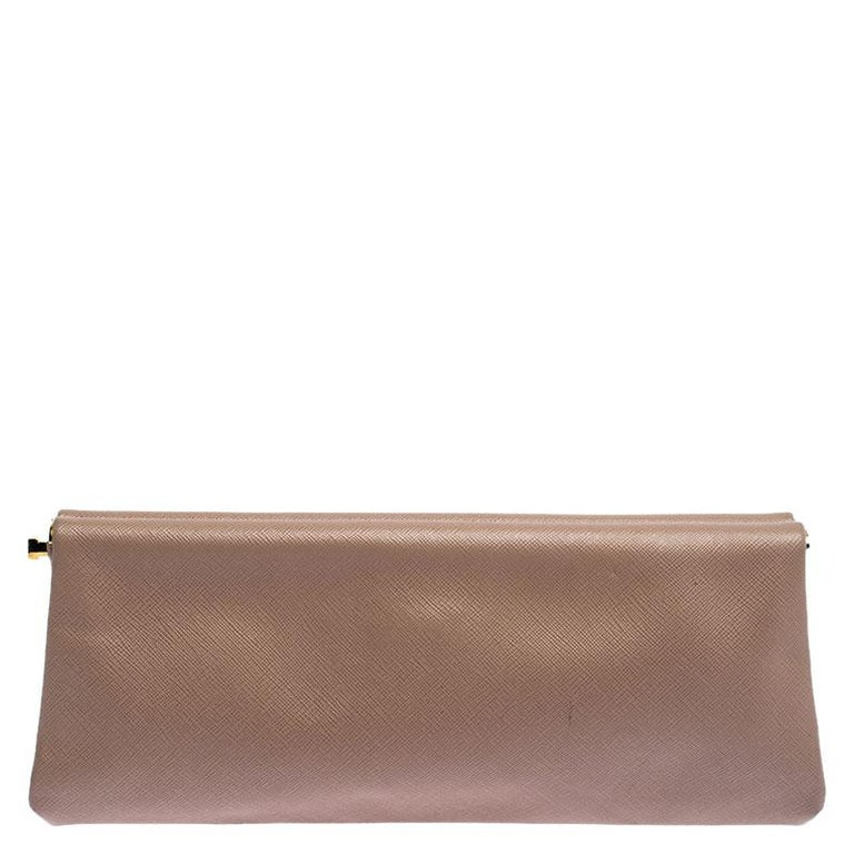 Expertly designed, this clutch from Prada has a framed body made from Saffiano leather. While the brand label in gold-tone adorns the front, a spacious interior makes the clutch functional. Complete your evening ensemble with this beautiful