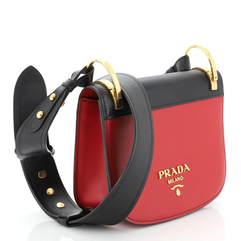 This Prada Pionniere Saddle Crossbody Bag City Calfskin Small, crafted from red leather, features an adjustable leather strap and gold-tone hardware. Its flap opens to a black leather interior with slip pocket.   Estimated Retail Price: