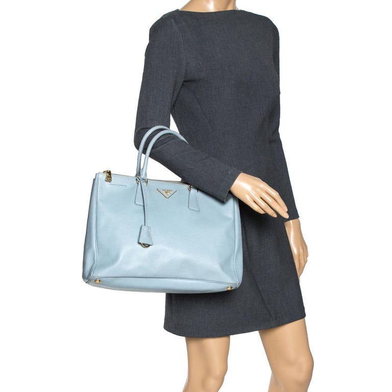 Feminine in shape and grand on design, this Double Zip tote by Prada will be a loved addition to your closet. It has been crafted from leather and styled minimally with gold-tone hardware. It comes with two top handles, two zip compartments, and a