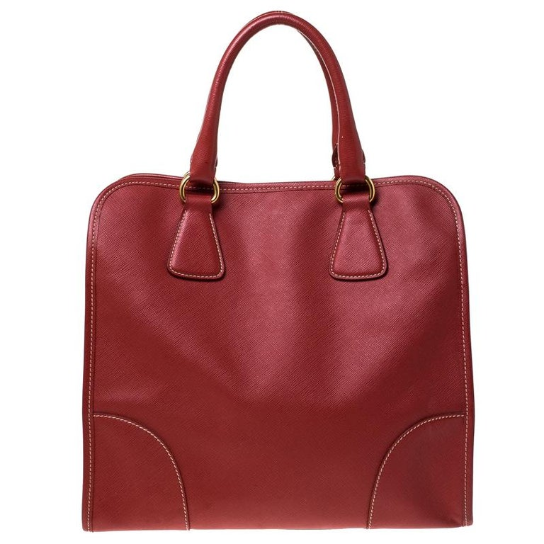 Flaunt an awesome style when you step out swaying this Prada satchel. It has been crafted from red Saffiano leather and held by two handles. The bag has a snap button that leads to a nylon interior equipped with pockets. Flaunting a structured body,
