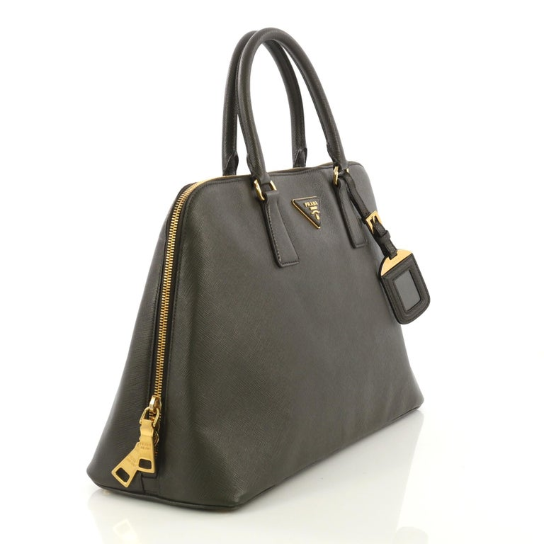 This Prada Promenade Bag Saffiano Leather Large, crafted from dark green saffiano leather, features dual rolled handles, triangle Prada logo, and gold-tone hardware. Its two-way zip closure opens to a black fabric interior with a center zip