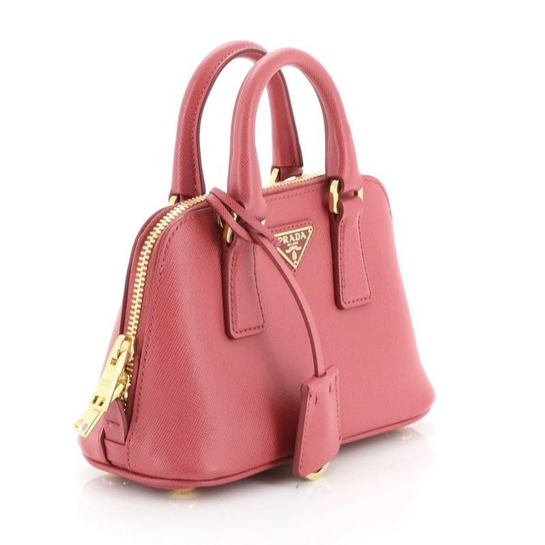 This Prada Promenade Bag Saffiano Leather Mini, crafted from pink saffiano leather, features dual rolled handles, triangle Prada logo, and gold-tone hardware. Its zip closure opens to a pink fabric interior with slip pocket.   Estimated Retail