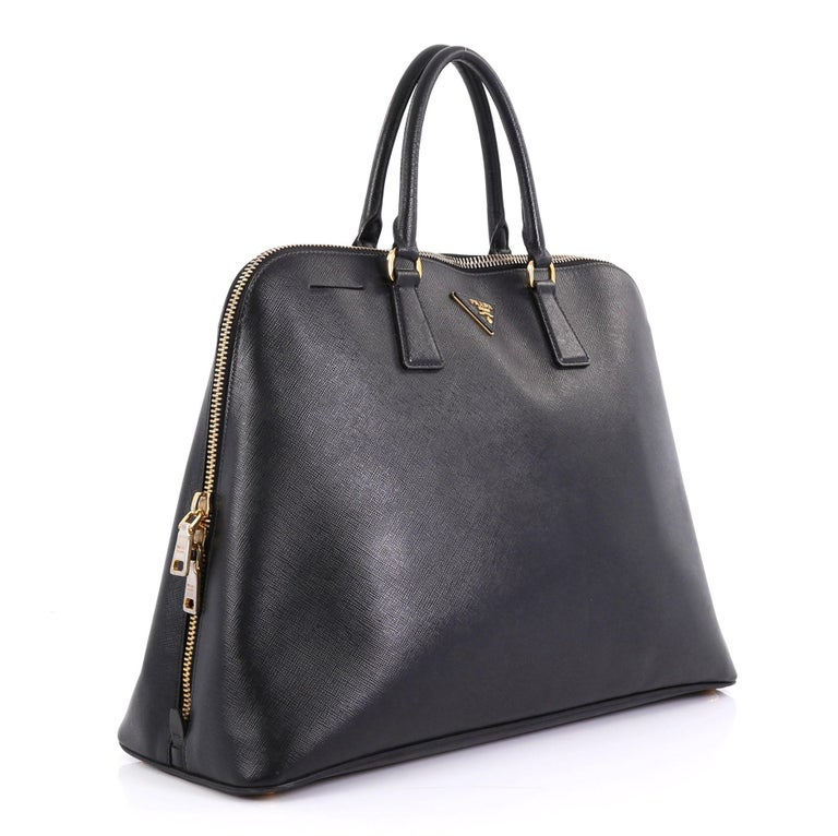 This Prada Promenade Bag Saffiano Leather XL, crafted from black saffiano leather, features dual rolled handles, protective base studs and gold-tone hardware. Its zip closure opens to a black fabric interior divided into two compartments with center