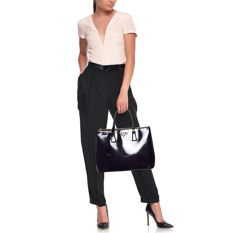 Feminine in shape and design, this Double Zip tote by Prada will be a loved addition to your closet. It is crafted from patent leather and styled minimally with gold-tone hardware. It comes with two top handles, two zip compartments, and a perfectly