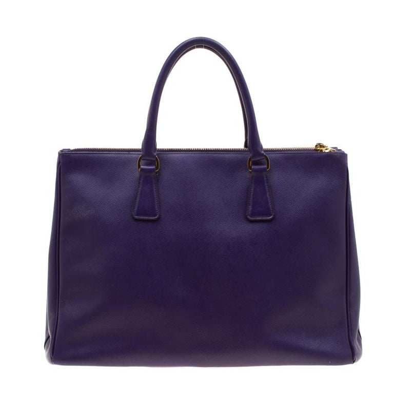 Featuring a grand design, this Double Zip tote by Prada will be a loved addition to your closet. This gorgeous bag, structured to perfection, is covered in a purple hue. It is constructed very carefully using the signature Saffiano Lux leather.