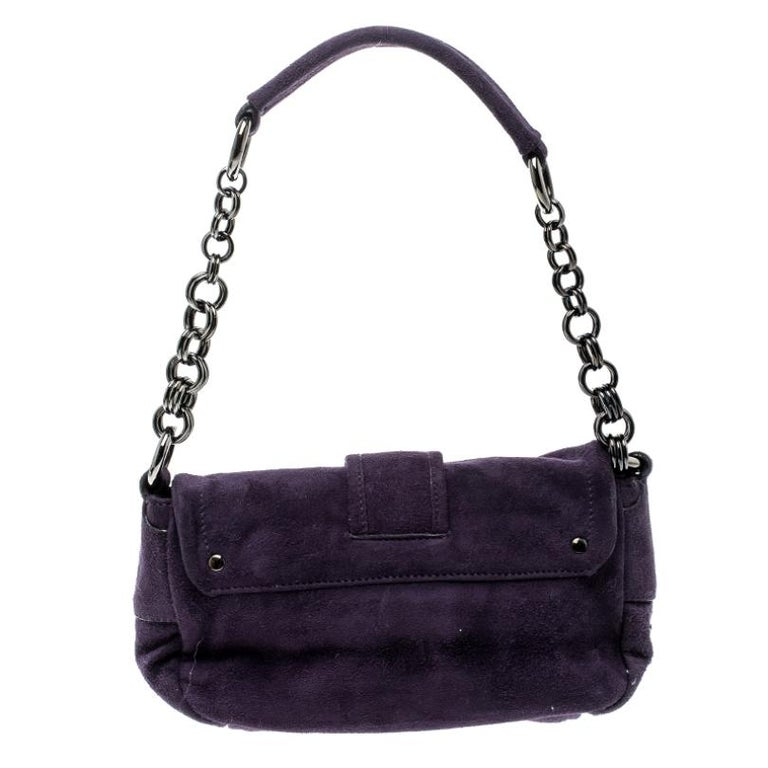 Get yourself this good-looking suede bag for a posh look. Prada has exclusively made this delicate piece in a classy purple colour with a buckle flap and a single chain handle. Complete with a nylon inlay, the bag is stylish and