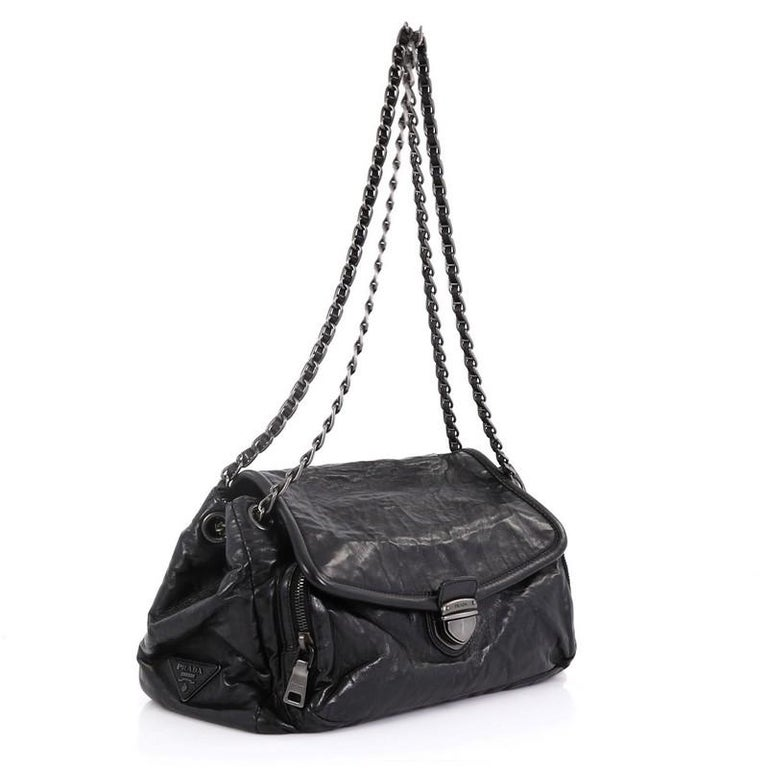 This Prada Pushlock Chain Flap Shoulder Bag Nappa Antique Medium, crafted in black nappa antique, features woven-in leather chain straps, exterior back slip pocket, zip pocket under its flap, and matte gunmetal-tone hardware. Its push-lock closure