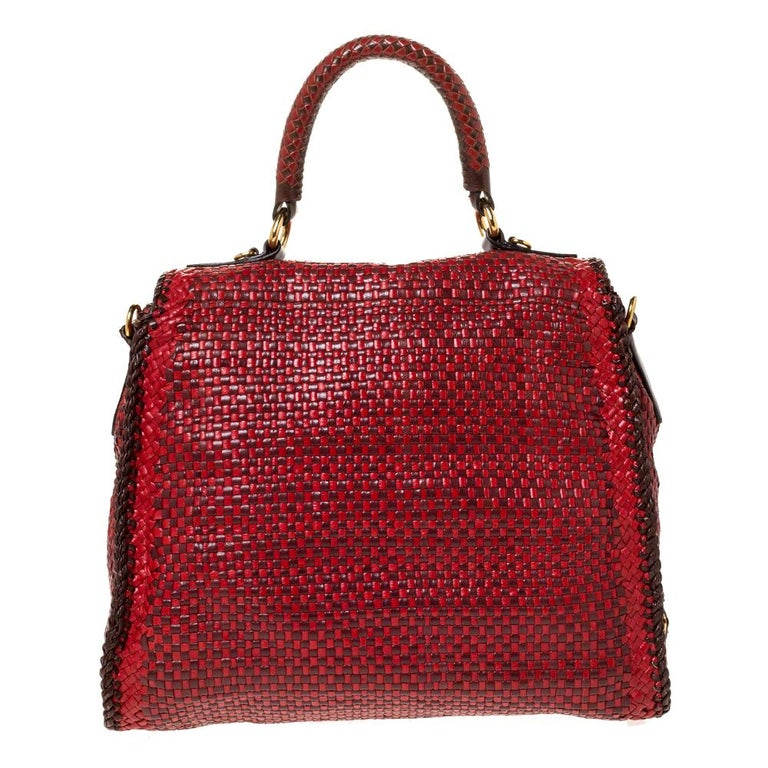 You'll love carrying this Madras bag by Prada. Made from red & brown woven leather, this bag features a single woven top handle supported with gold-tone rings, a flap with brand detailed push-lock closure, and a detachable shoulder strap. The
