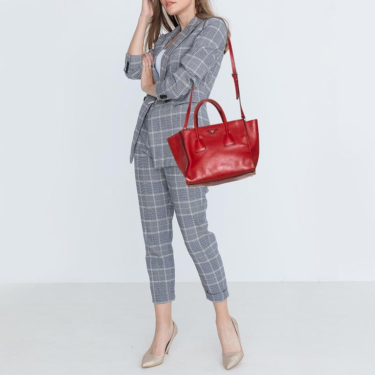 Add some effortless style and luxury to your everyday looks with this stunning Prada tote. Crafted in red-hued leather, this bag can store all that you need through the day or for work in its large middle compartment and two zippered compartments.