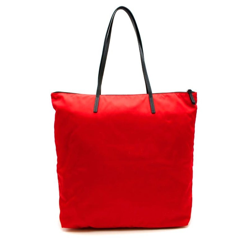Prada Red Nylon & Saffiano Leather Tote Bag  -Made of Pradas now iconic nylon  -Luxurious signature saffiano leather shoulder straps and details  -Prada triangular logo hardware to the front  -Zip fastening to the top -Zipped interior pocket