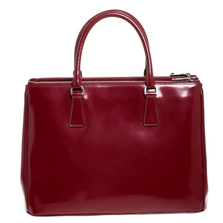 Feminine in shape and grand on design, this Double Zip tote by Prada will be a loved addition to your closet. It has been crafted from red patent leather and styled minimally with silver-tone hardware. It comes with two top handles, two zip