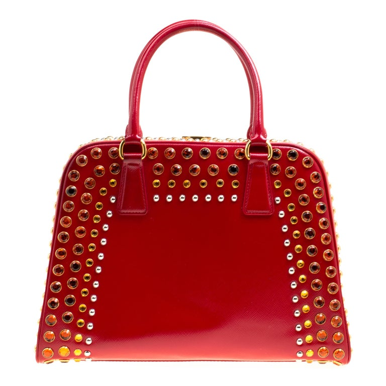 This marvelously designed top handle bag from Prada is the epitome of charm and style. Everything about the bag speaks opulence and a glamorous finish. Sculpted in a pyramid frame style, the bag is crafted from shiny red patent leather with