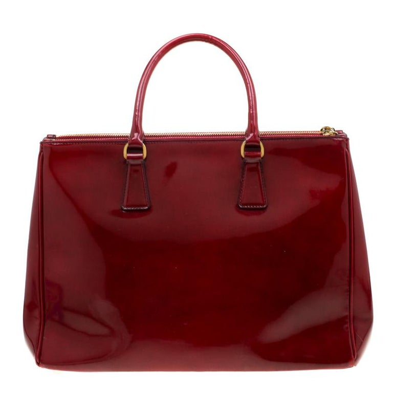 Feminine in shape and grand on design, this Double Zip tote by Prada will be a loved addition to your closet. It has been crafted from patent leather and styled minimally with gold-tone hardware. It comes with two top handles, two zip compartments