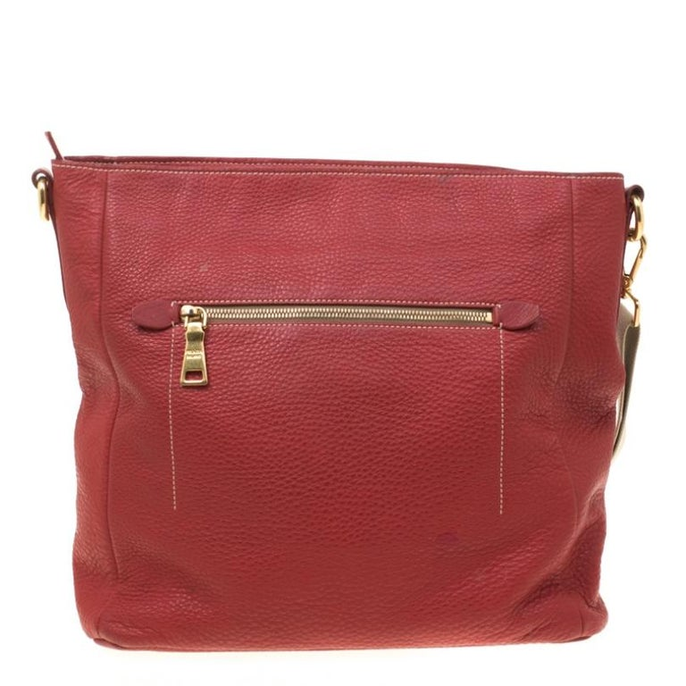 Prada presents an expertly crafted messenger bag. Made from red pebbled leather, the bag features a shoulder strap and zip pockets both at the front and back. The well-sized interior is lined with nylon and secured by a zip closure. The bag is