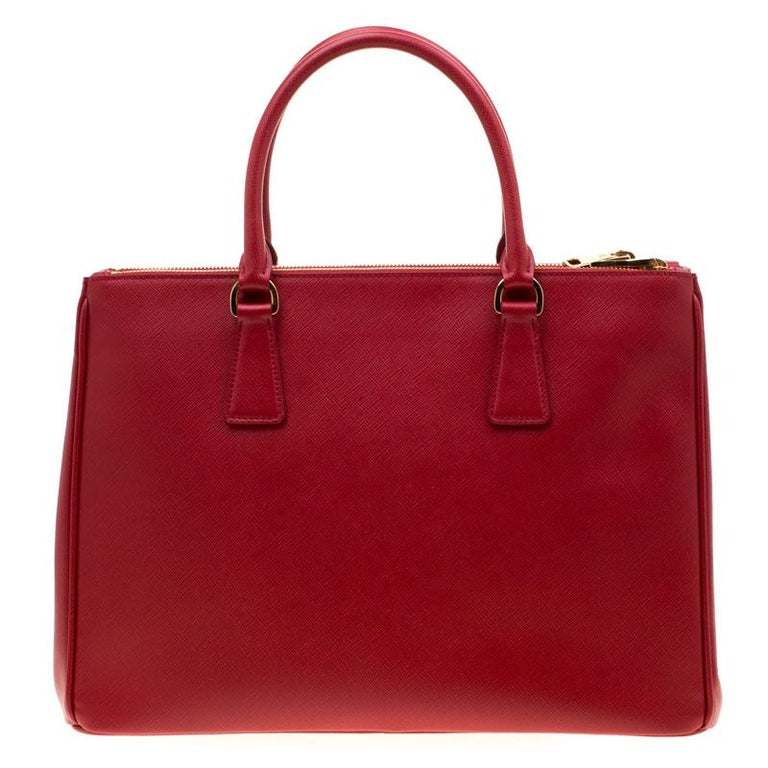 Feminine in shape and grand on design, this double zip tote by Prada will be a loved addition to your closet. It has been crafted from red leather and styled minimally with gold-tone hardware. It comes with two top handles, two zip compartments and
