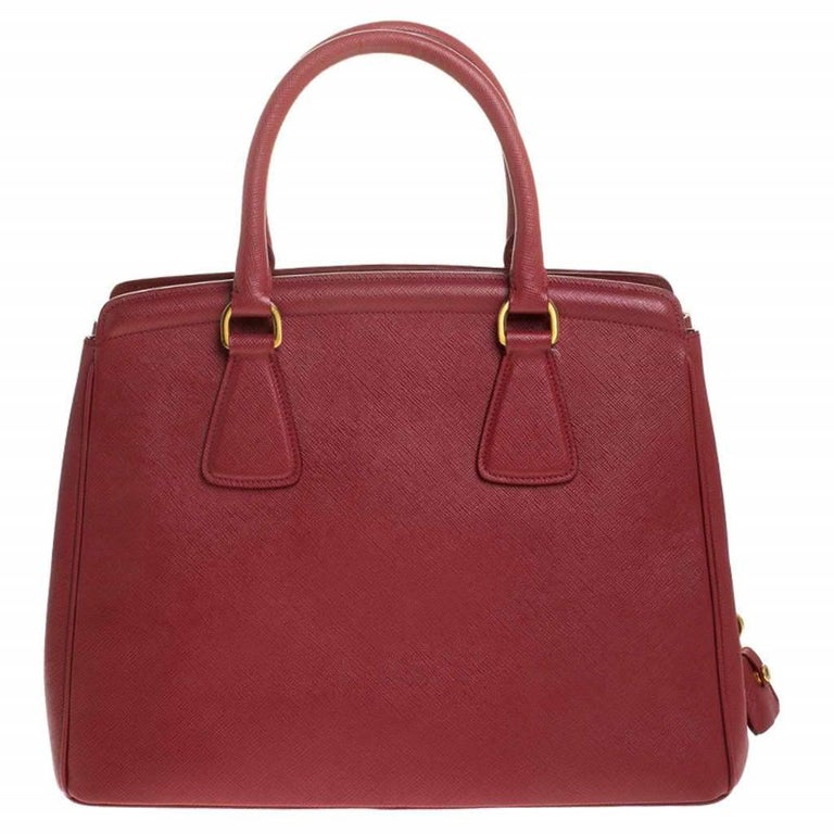Masterfully created, this Prada tote is a style icon. Designed in a Saffiano Lux leather body, it exudes style and class in equal measures. This delightful red piece is held by two top handles and equipped with a spacious nylon interior.  Includes:
