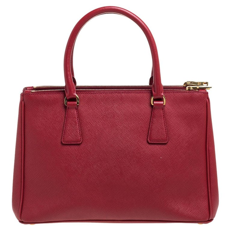 High on style and class, this Galleria Double Zip tote by Prada will be a cherished addition to your closet. It has been crafted from Saffiano Lux leather in a red shade and styled minimally with gold-tone hardware. It comes with dual handles and a