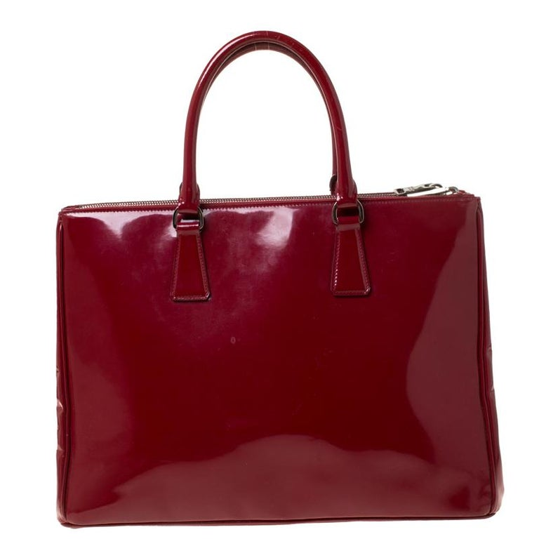 Feminine in shape and grand on design, this Double Zip tote by Prada will be a loved addition to your closet. It has been crafted from patent leather and styled minimally with silver-tone hardware. It comes with two top handles, two zip compartments