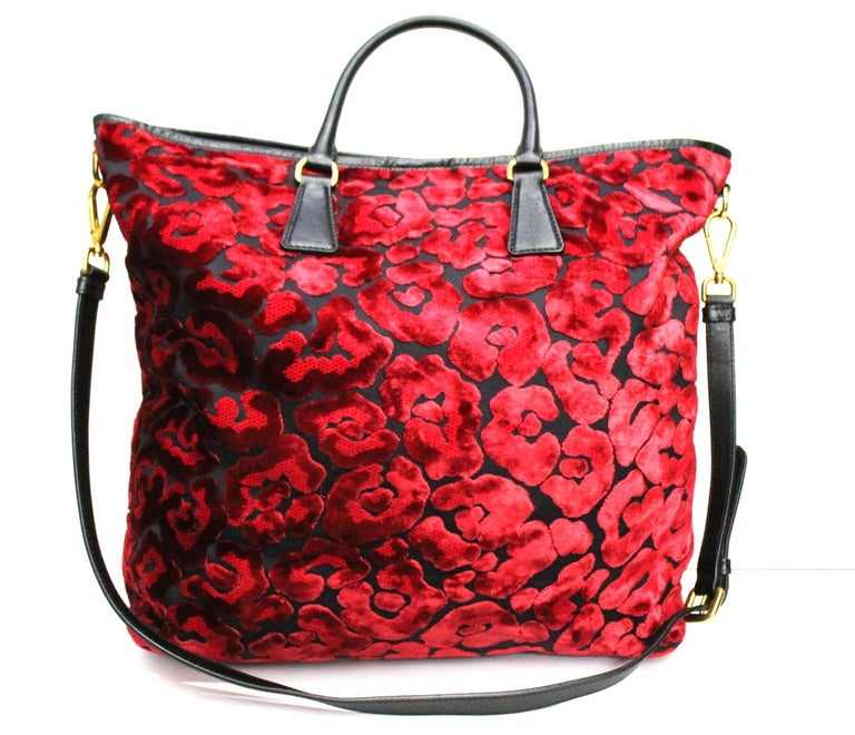 Prada shopper made of red suede with handles and shoulder strap in black leather and gold hardware.  Internal closure with large button.  CONDITIONS LIKE NEW.