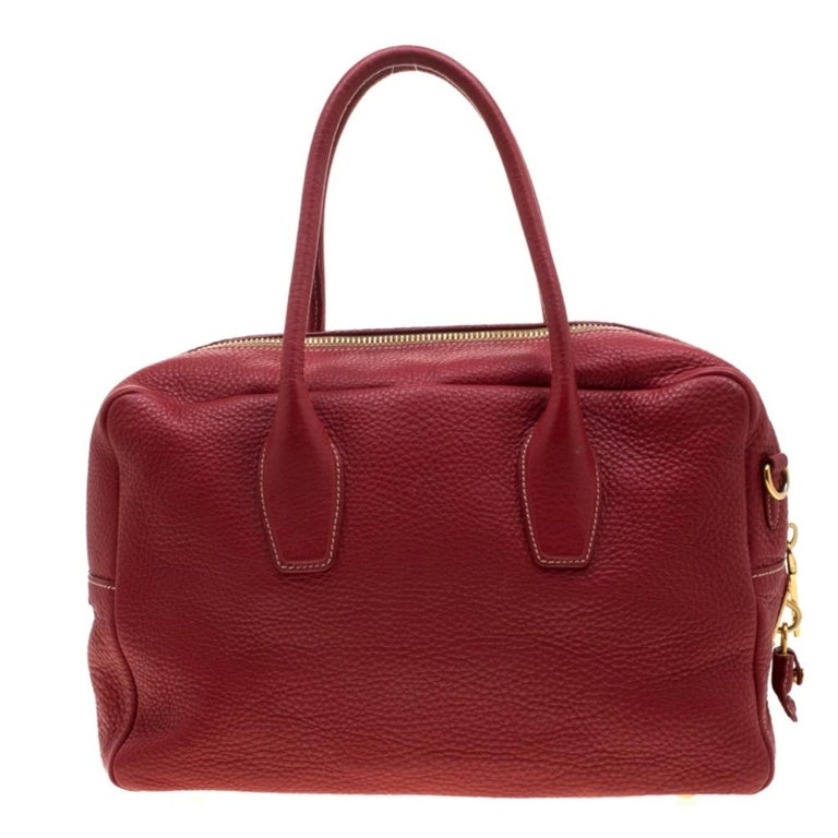 Crafted from Red Vitello Daino leather, this handbag features Prada's iconic logo, top zip closure and gold-tone hardware. This bag is accentuated with dual top handles along with a detachable and adjustable shoulder strap and leather clochette to