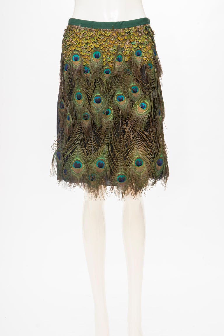 """Prada Runway Spring 2005 black cotton pleated knee-length skirt with appliquéd peacock feather accents throughout and snap closures at side.  IT. 38, US.2  Skirt: Waist 29"""", Hip 38"""", Length 22"""""""