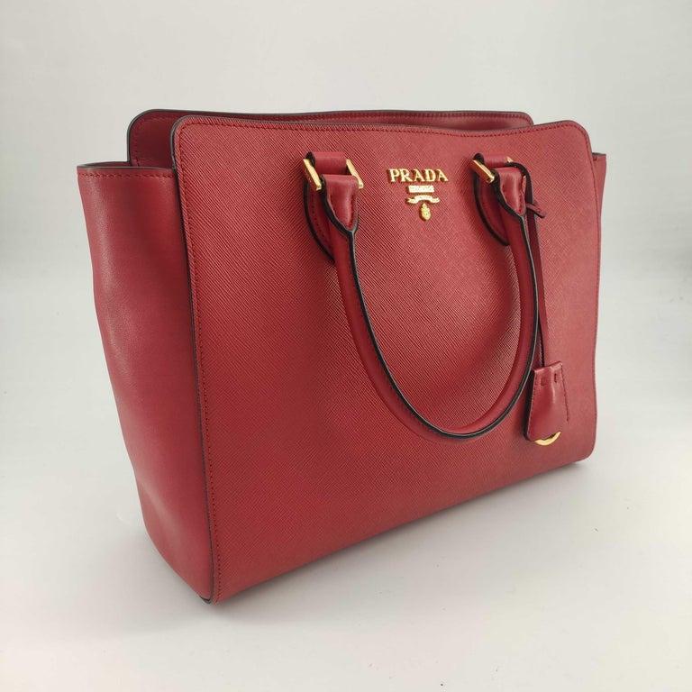 - Designer: PRADA - Model: Saffiano - Condition: Very good condition.  - Accessories: Dustbag, Authenticity Card - Measurements: Width: 29cm, Height: 24cm, Depth: 10cm - Exterior Material: Leather - Exterior Color: Red - Interior Material: Cloth -
