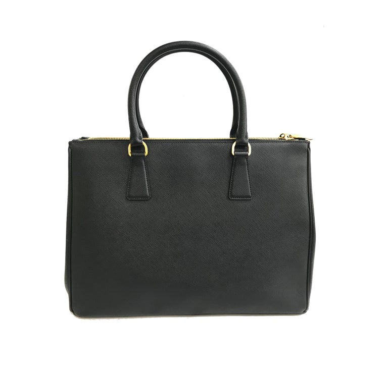 Prada's Galleria Saffiano tote is a perfectly prim addition to your accessories edit. Crafted from textured black calf leather, this design is finished with dainty top handles and golden hardware. Double storage compartments leave ample room for