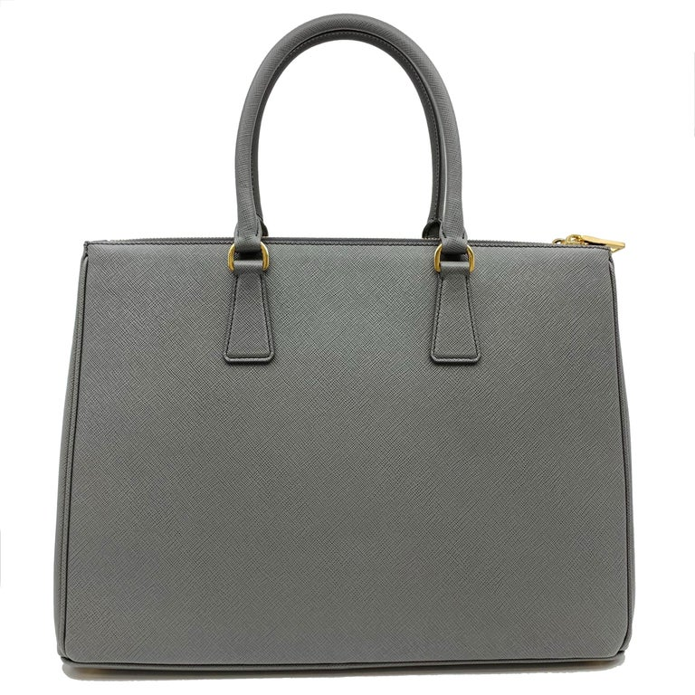 Prada's Galleria saffiano tote is a perfectly prim addition to your accessories edit. Crafted from textured gray calf leather, this design is finished with dainty top handles and golden hardware. Double storage compartments leave ample room for